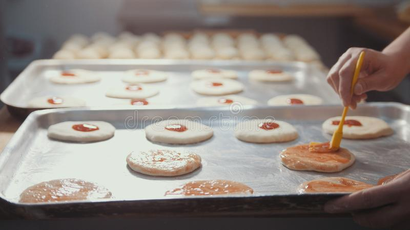 Les cuisiniers dans la cuisine préparent une mini pizza, placent la sauce tomate photographie stock libre de droits