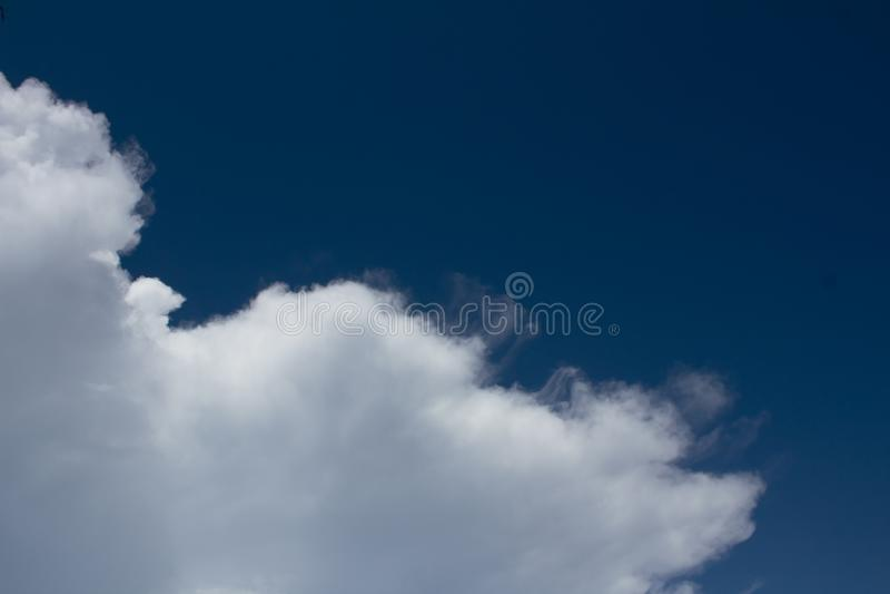 Les cumulus blancs volent sur le ciel bleu-foncé image stock