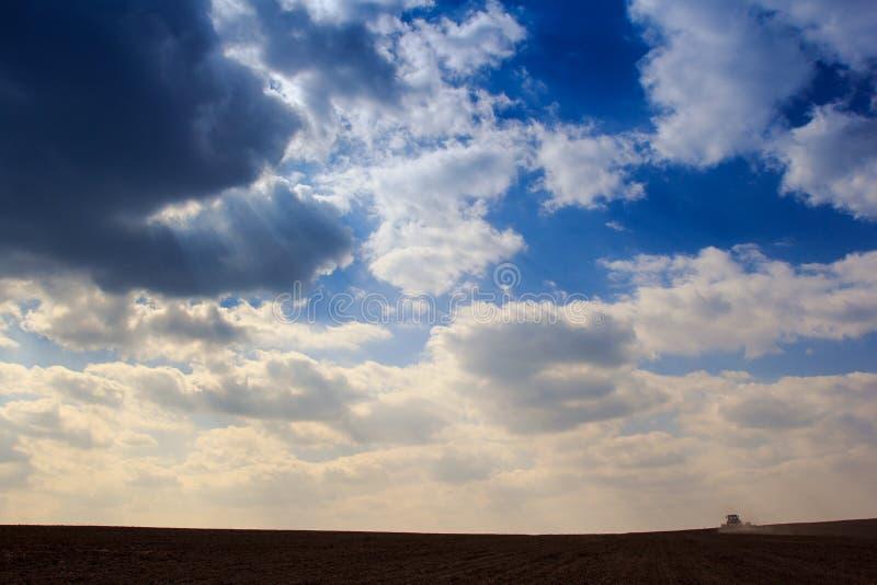les cumulus de ciel bleu au-dessus de l'obscurité ont labouré le champ photo libre de droits