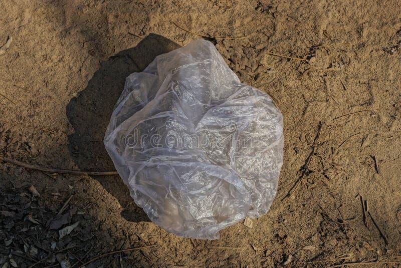 Les déchets d'un sac gris vide de cellophane se trouvent sur la terre sèche brune images libres de droits