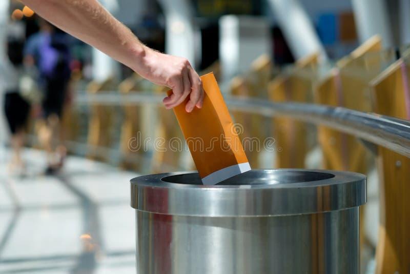 Les déchets de papier mettant dans réutilisent la poubelle image stock