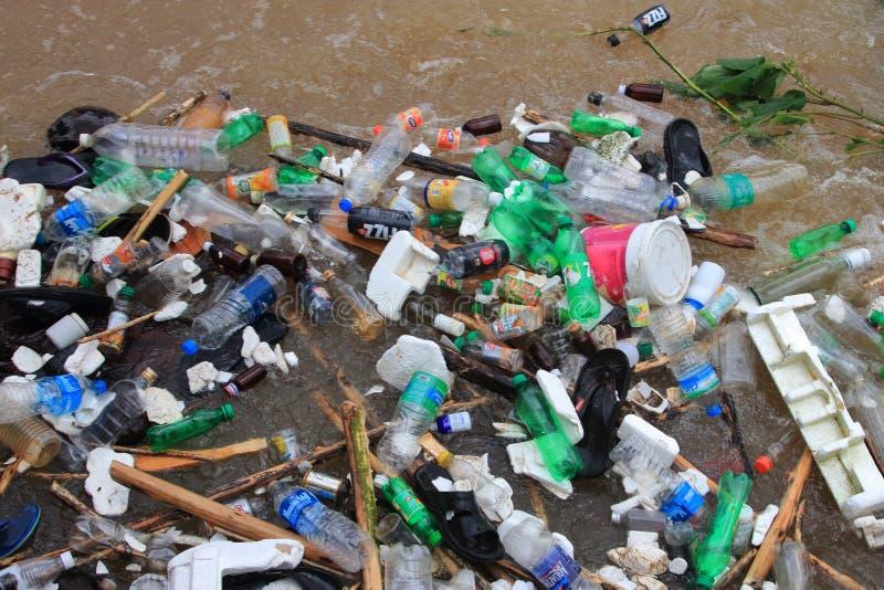 Les déchets en plastique traversent les eaux d'inondation photographie stock libre de droits