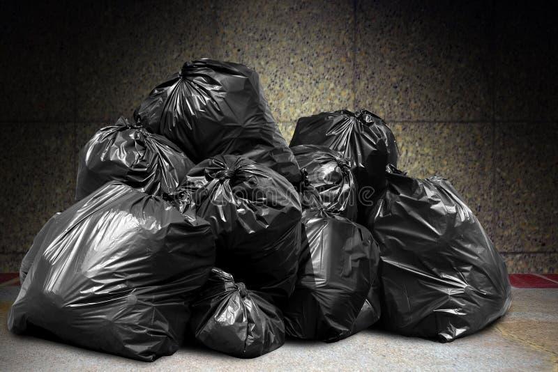 Les déchets sont des sorts de pile vident, les déchets de noir de beaucoup de déchets de sachets en plastique au mur en béton, po image stock