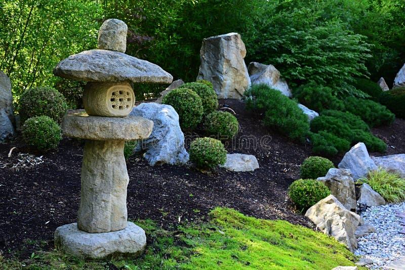 Les décorations en pierre et les buissons cultivés dans MU-Shin dénomment le jardin de l'Extrême Orient image libre de droits