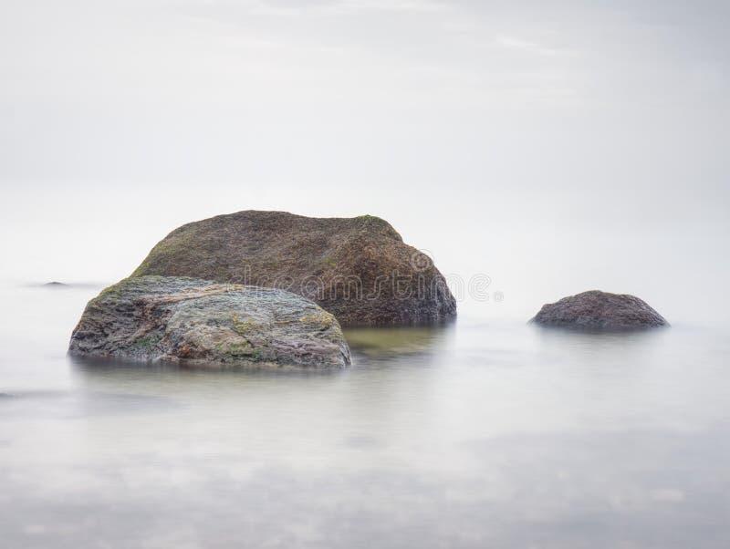 Les défis pierreux de côte vers l'océan dégagent le ciel avec Sun brouillé dans le humidité élevé images libres de droits