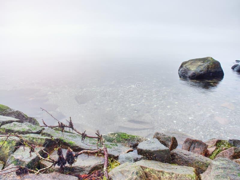 Les défis pierreux de côte vers l'océan dégagent le ciel avec Sun brouillé dans le humidité élevé photo libre de droits