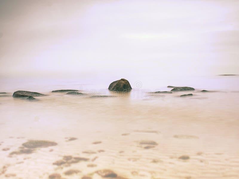 Les défis pierreux de côte vers l'océan dégagent le ciel avec Sun brouillé dans le humidité élevé photographie stock libre de droits
