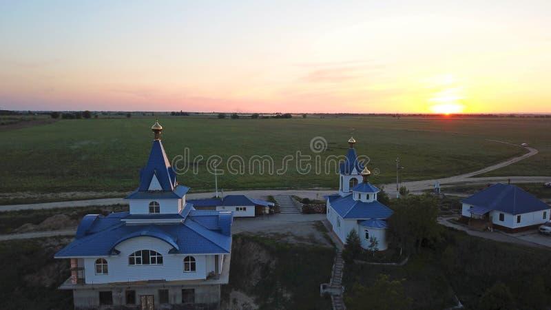 Les dômes d'or de l'église au coucher du soleil Champs verts avec des pavots tout autour images libres de droits