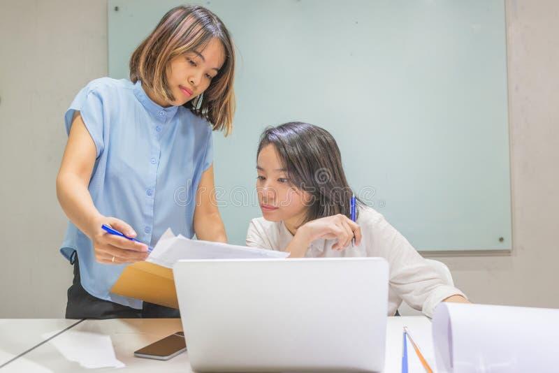 Les dames asiatiques de bureau discutent au sujet du rapport financier photographie stock libre de droits