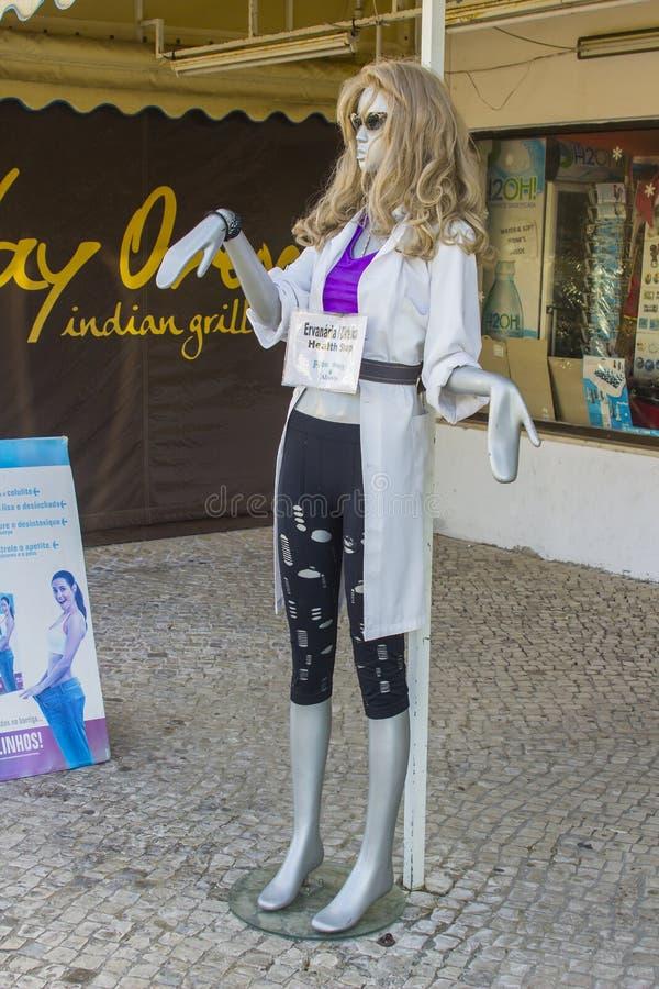 Les dames façonnent le mannequin sur l'affichage dans une porte de boutique sur la bande dans la station de vacances portugaise d photo libre de droits