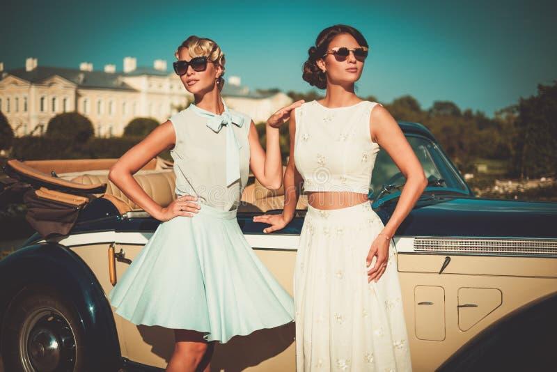 Les dames s'approchent du convertible classique photos stock