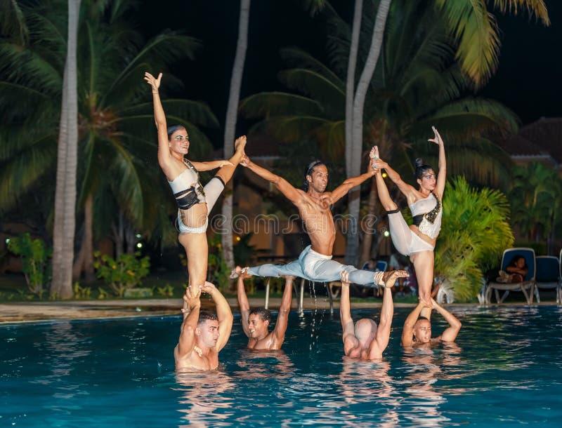 Les danseurs professionnels exécutant l'eau montrent dans la piscine extérieure photos libres de droits