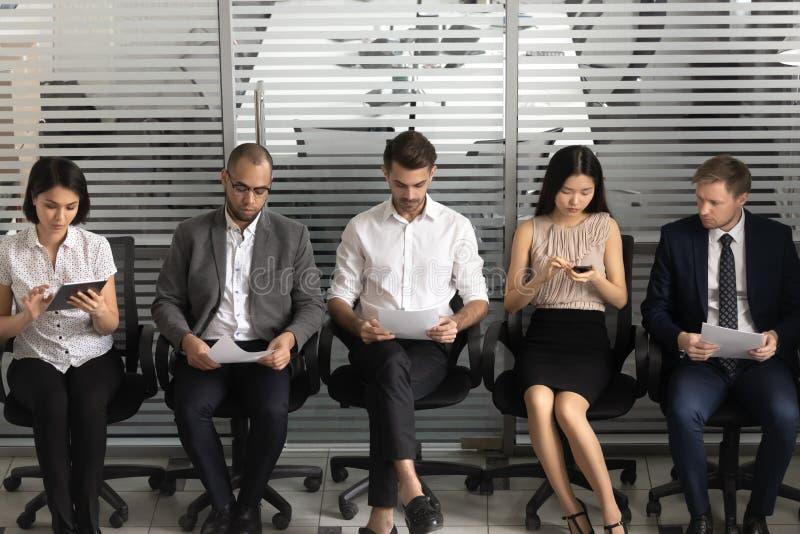 Les demandeurs divers s'asseyent sur des chaises dans la rangée dans la salle d'attente images stock