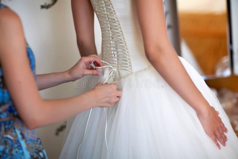 Les demoiselles d'honneur aident la jeune mariée images libres de droits