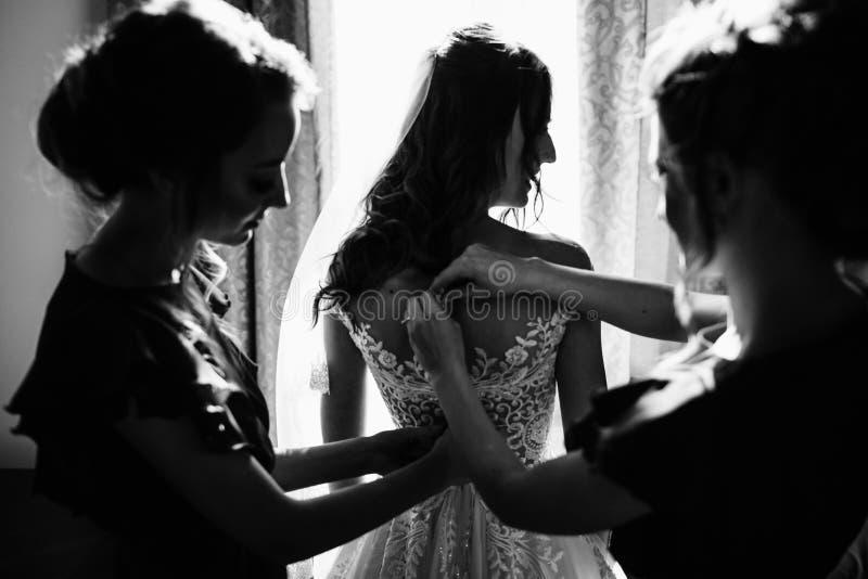 Les demoiselles d'honneur tourbillonnent le voile du ` s de jeune mariée tandis qu'elle sourit photographie stock libre de droits