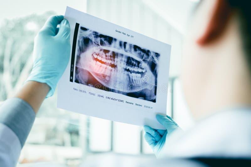 Les dentistes masculins asiatiques analysent des images de rayon X des patients au Th photographie stock libre de droits