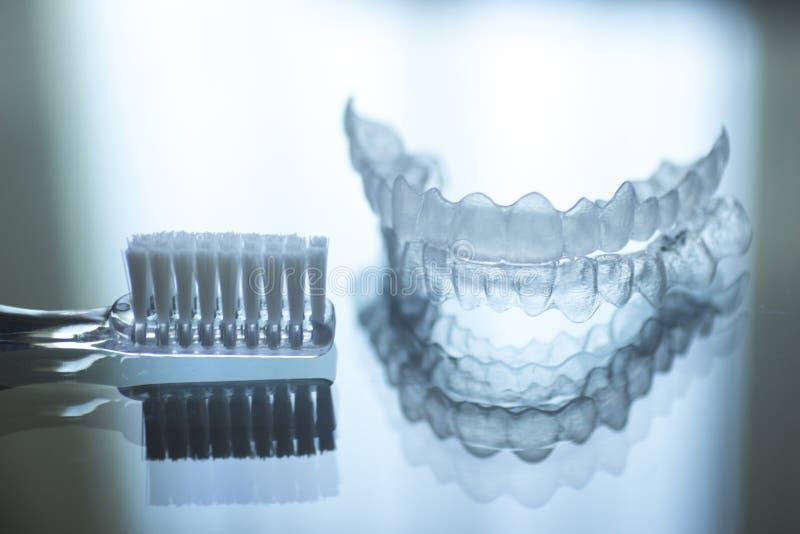 Les dents dentaires invisibles encadre des arrêtoirs et le toothbrus de dispositifs d'alignement photographie stock