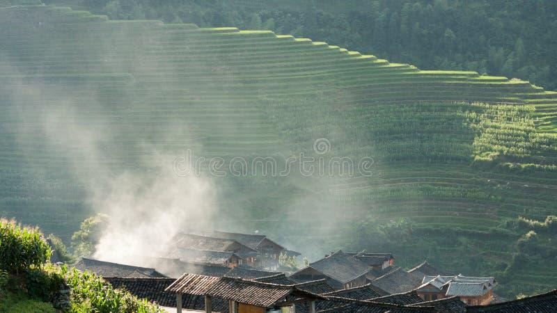 Les dessus de toit et la fumée dans des terrasses de riz aménagent la Chine en parc image stock