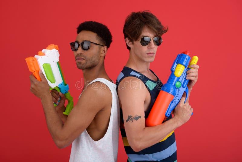 Les deux amis beaux d'hommes avec de l'eau jouent des armes à feu photos stock
