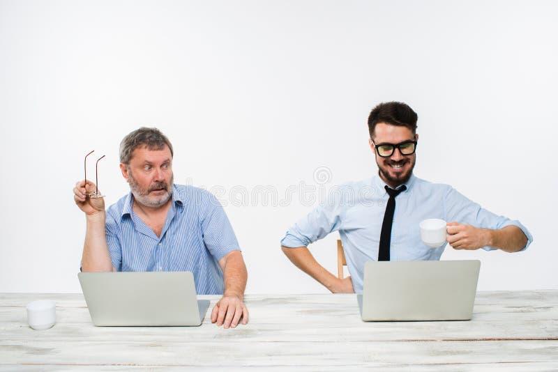 Les deux collègues travaillant ensemble au bureau sur le fond blanc image libre de droits