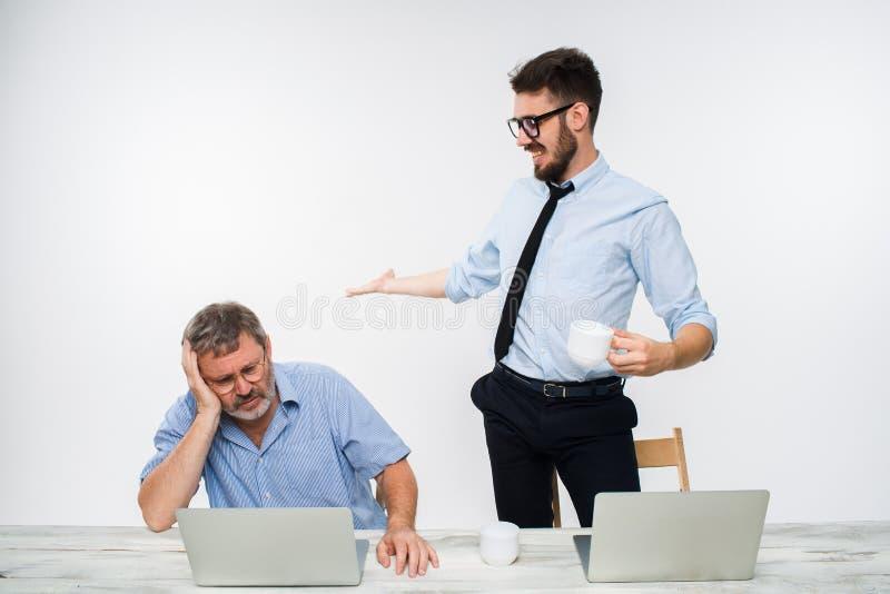 Les deux collègues travaillant ensemble au bureau sur le fond blanc photo stock
