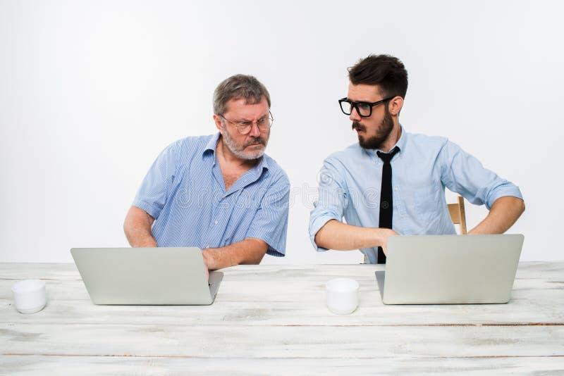 Les deux collègues travaillant ensemble au bureau sur le fond blanc photographie stock