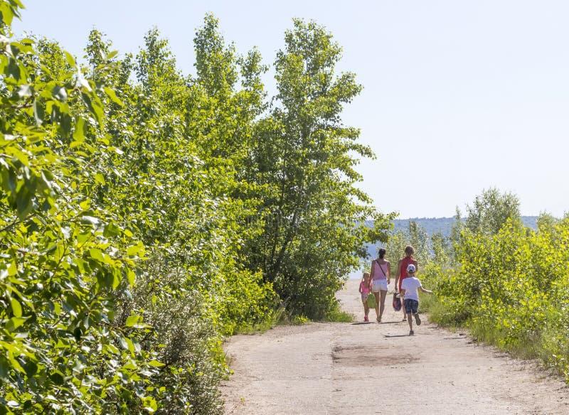 Les deux femmes et les deux enfants marchent sur la route à la plage un jour ensoleillé photos libres de droits