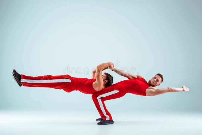 Les deux hommes caucasiens acrobatiques gymnastiques tout bien pesé posent image libre de droits