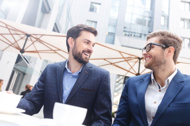 Les deux hommes d'affaires gais communiquent dans le restaurant photos stock