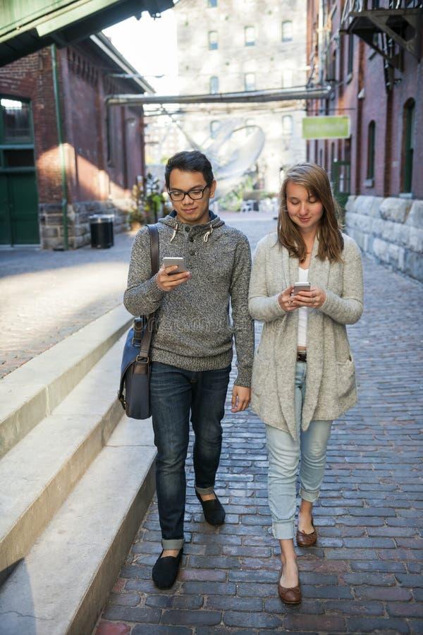 Les deux jeunes avec les téléphones intelligents image libre de droits