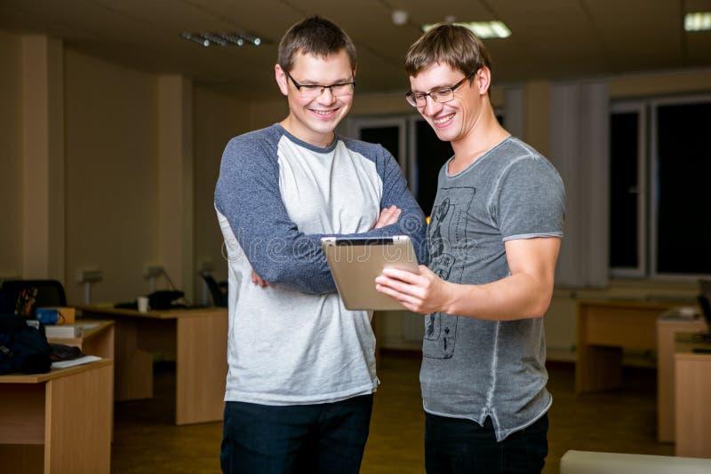 Les deux jeunes discutent un projet dans le bureau Se tenant l'un à côté de l'autre, l'un d'entre eux indique l'autre au sujet de photographie stock libre de droits
