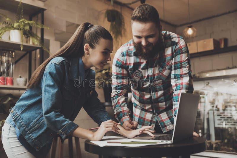 Les deux jeunes travaillant sur un ordinateur portable en café images libres de droits