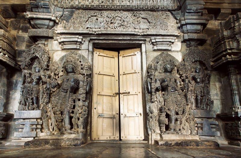 Les dieux indous à la porte d'entrée au style traditionnel lapident le temple de Hoysaleswara, structure du 12ème siècle, Inde image libre de droits