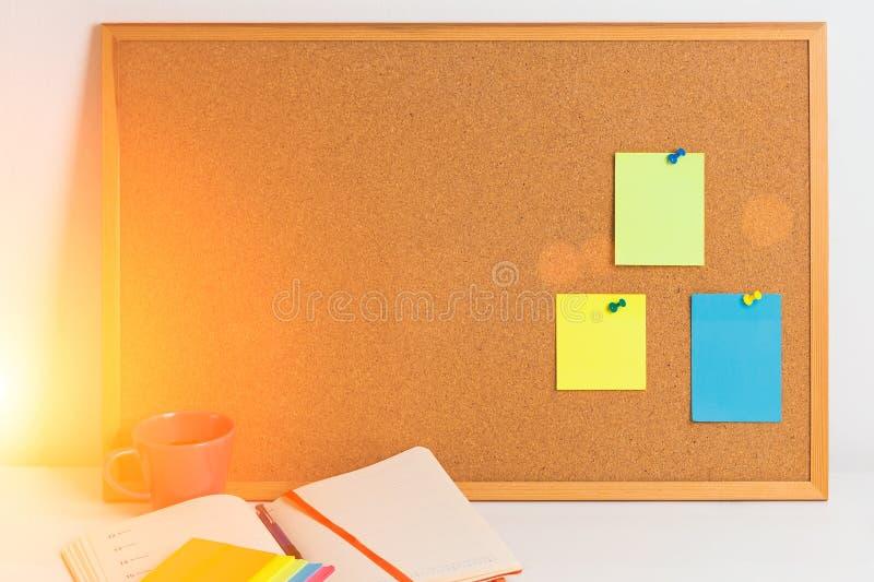 Les différents autocollants colorés pined sur le corkboard avec le bloc-notes et le coffe sur la table en bois blanche, horizonta photo libre de droits