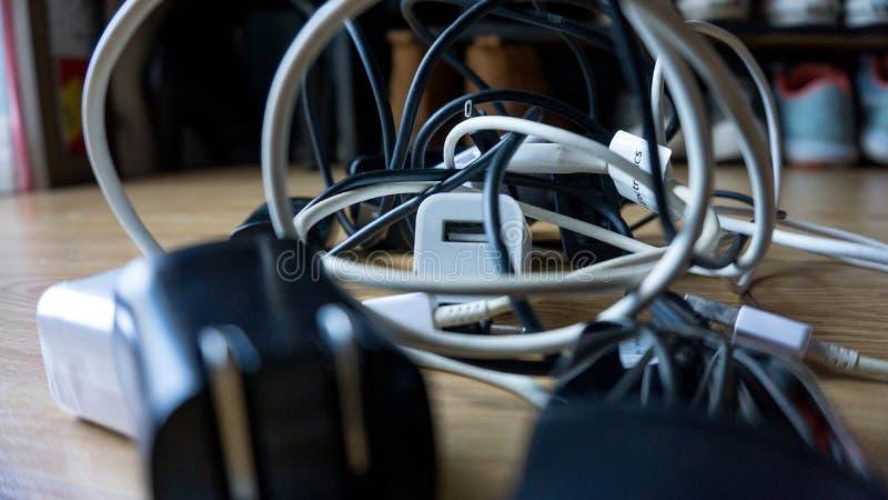Les différents chargeurs noirs et blancs d'usb de câbles et câble embrouillé et dans le chaos photographie stock libre de droits