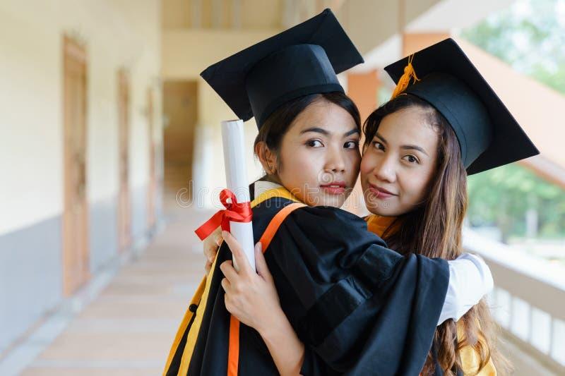 Les diplômés féminins d'université célèbrent heureusement après accompli et ont reçu le certificat de degré de diplôme dans la cé photo stock