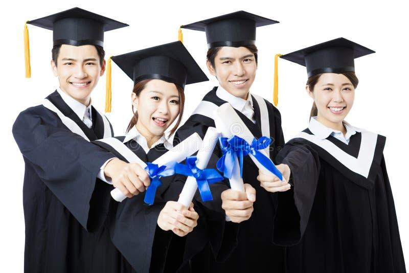 Les diplômés d'université dans l'obtention du diplôme habille la position et le sourire image libre de droits