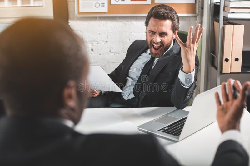 Les directeurs irrités se disputent dans le bureau photographie stock