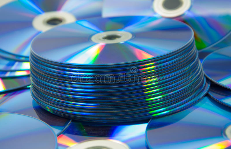 les disques compacts colorés ont placé du DVD dispersé sur une table images libres de droits