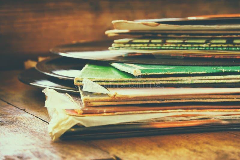 Les disques empilent avec le disque sur le dessus au-dessus de la table en bois Vintage filtré image stock