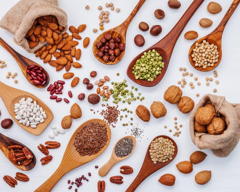 Les divers légumineuses et coquilles de noix dans des cuillères et chanvre aimables renvoient des sacs images stock