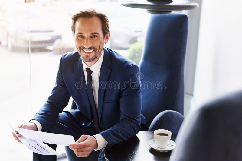 Les documents heureux de lecture d'homme d'affaires est café confortable photos libres de droits