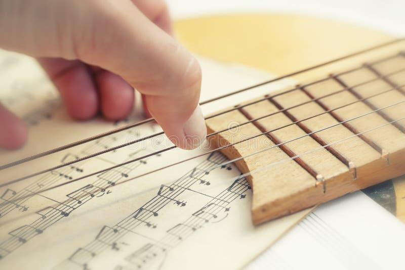 Les doigts conceptuels musicaux de composition des doigts heurtent les ficelles de la guitare dans la perspective du papier music photo stock
