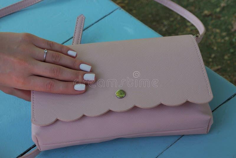 Les doigts de fille se trouvent sur une bourse rose sur une table bleue photos stock