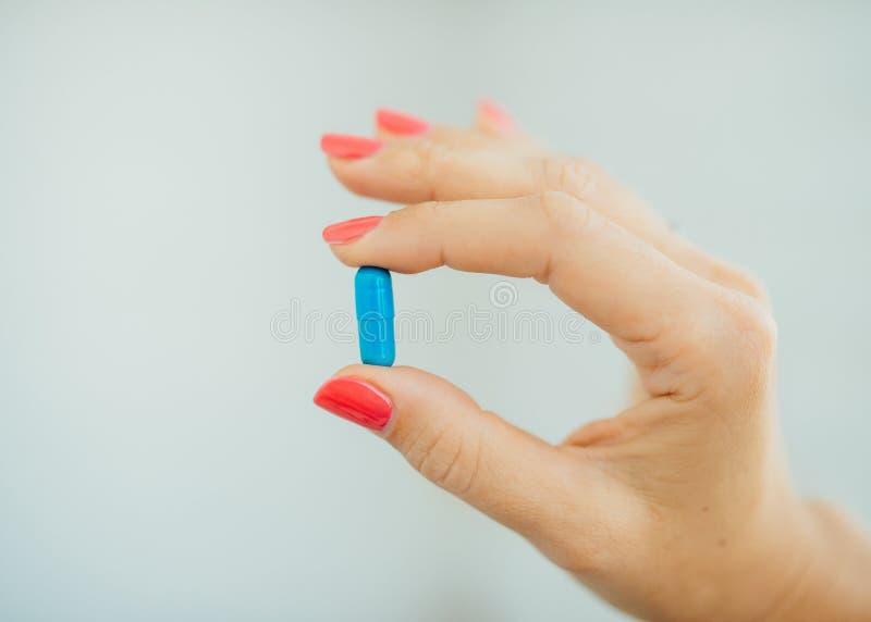 Les doigts des femmes avec la manucure rose prenant le bleu photo libre de droits