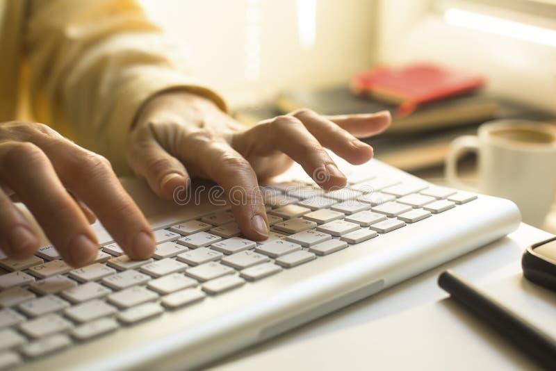 Les doigts des femmes dactylographiant sur le clavier d'ordinateur portable travail images stock