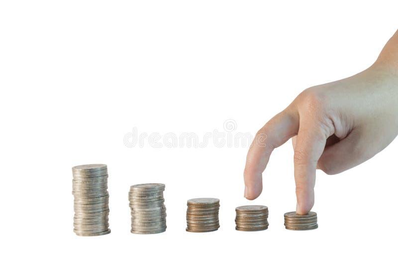 Les doigts intensifient sur la rangée des pièces de monnaie que les piles ont isolé le fond blanc photos stock