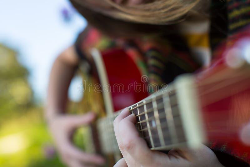 Les doigts sur les ficelles se ferment, fille jouant la guitare acoustique photo stock
