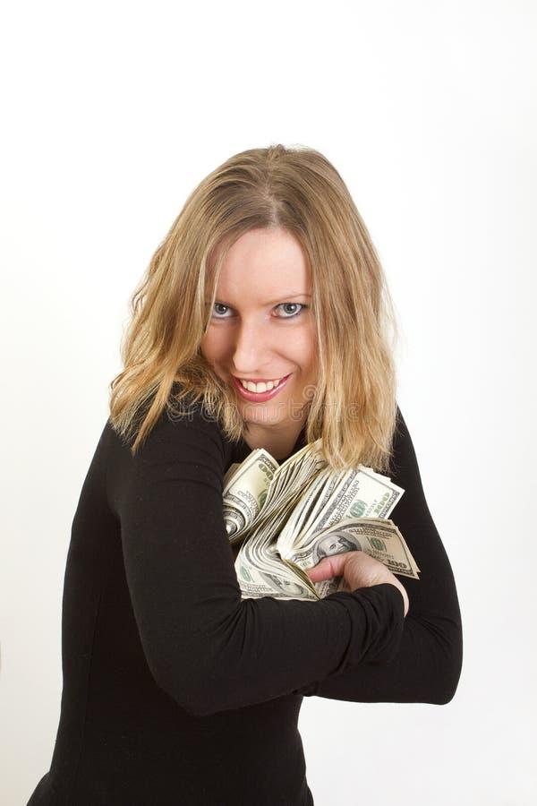 Les dollars de dissimulation de jeune femme et ont le visage avide photographie stock libre de droits