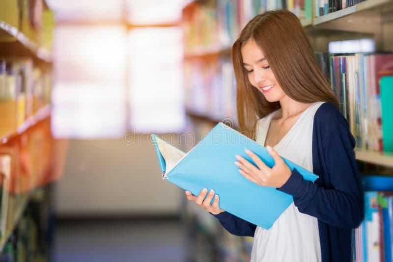 Les données asiatiques de recherche de dame d'étudiant pour rédigent un rapport dans la bibliothèque photographie stock libre de droits